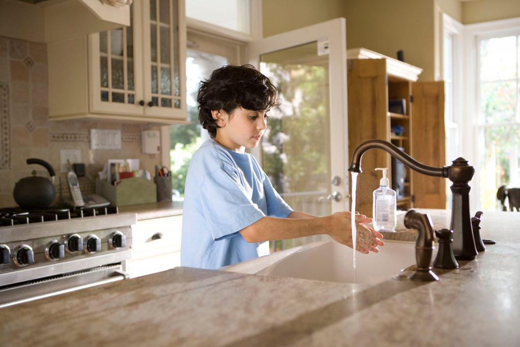 boy with blue shirt washing hand in kitchen