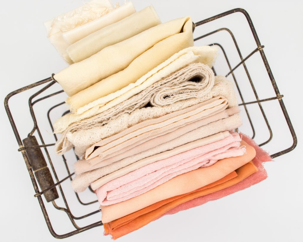 orange, yellow, and cream towels inside wire basket