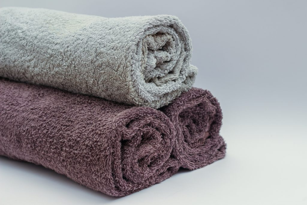 3 purple gray towels rolled and stacked