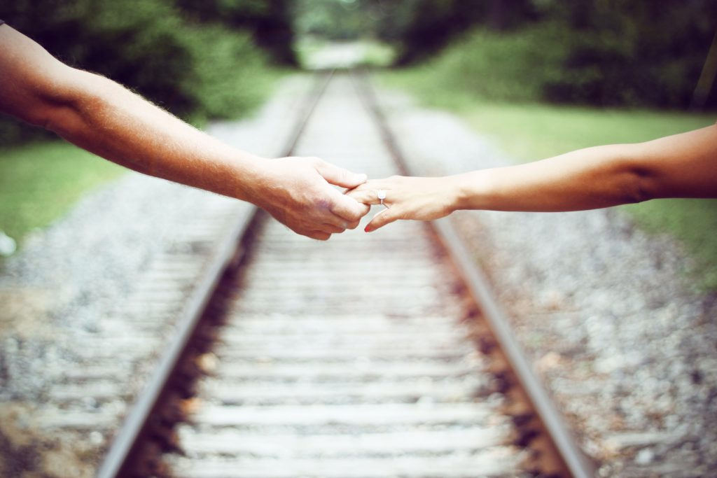hands holding over a railroad track in the background