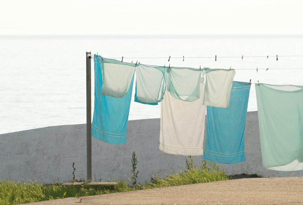 blue and white sheets hanging on wire outside