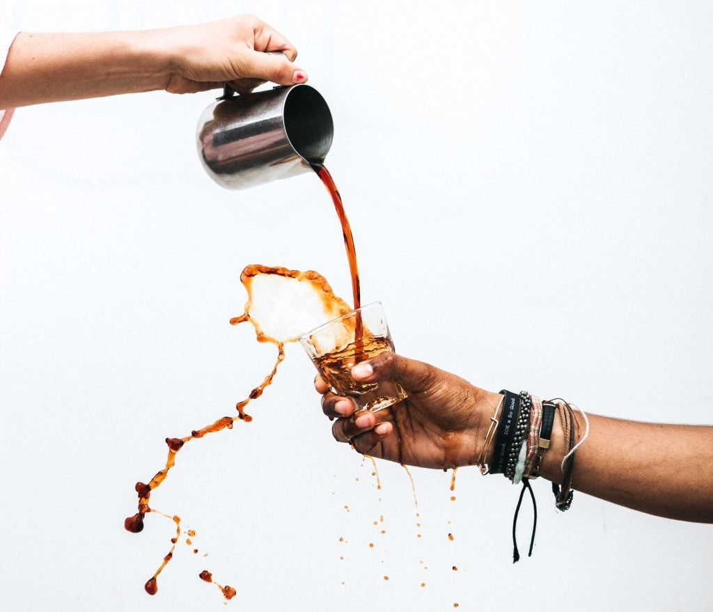 coffee being poured in cup held by someone