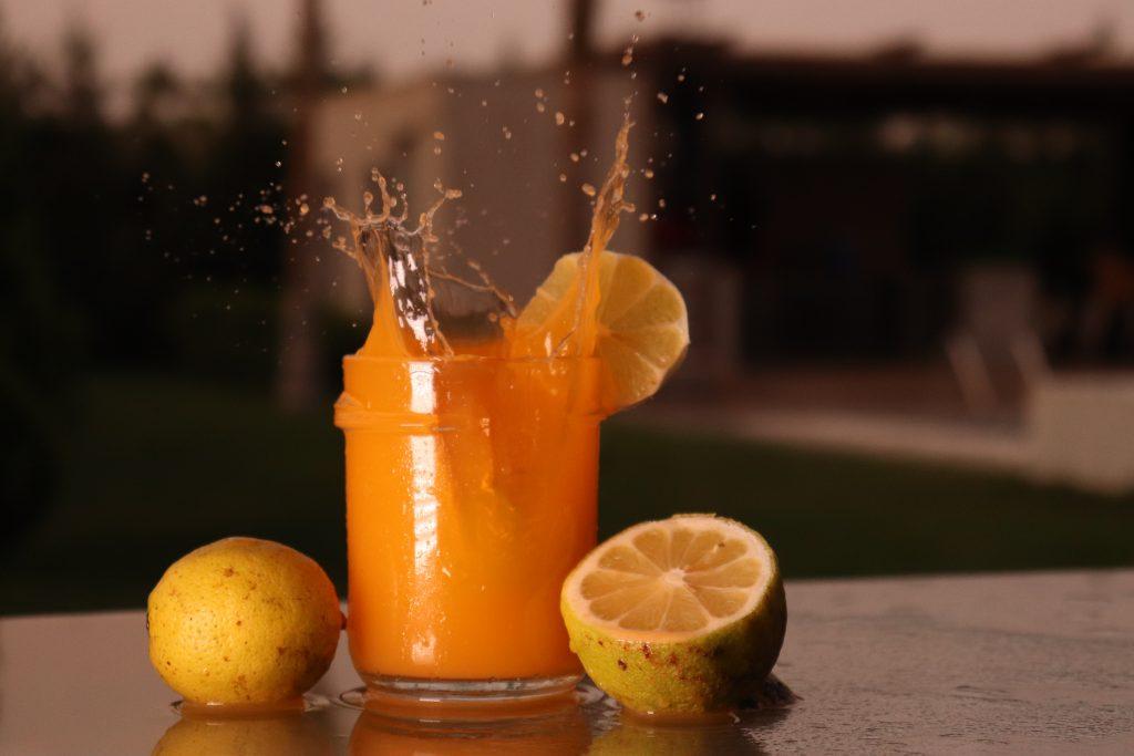 orange fruit juice splashing in glass